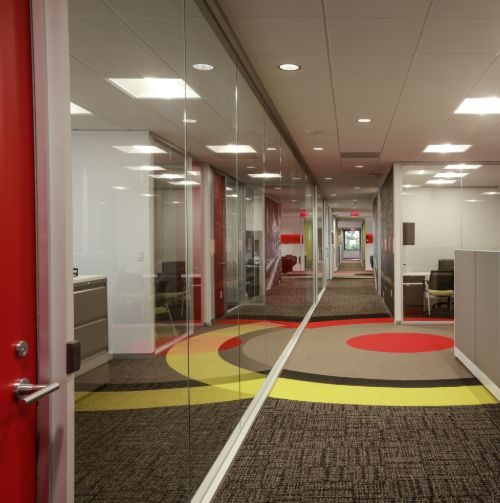 tejas tubular hallway with glass lined office windows on left hand side and bullseye logo pattern on carpet