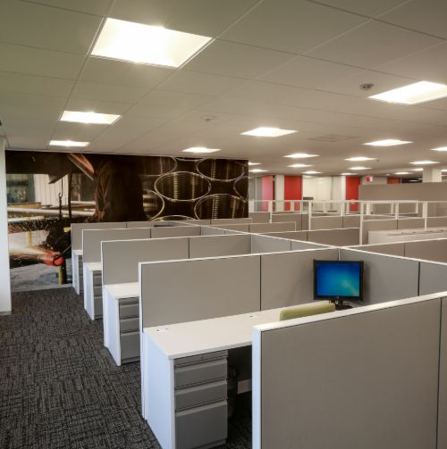 overview of main office space with multiple desks and cubicles