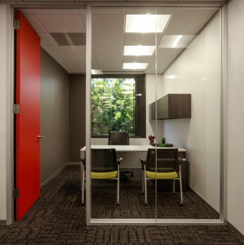 commercial office with grey wall, orange door and large window