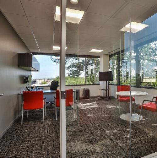 large corner office with orange chairs and windows lining outside corners