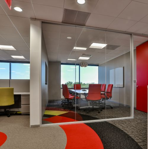 conference room containing eight, plush orange chairs and floor to ceiling window